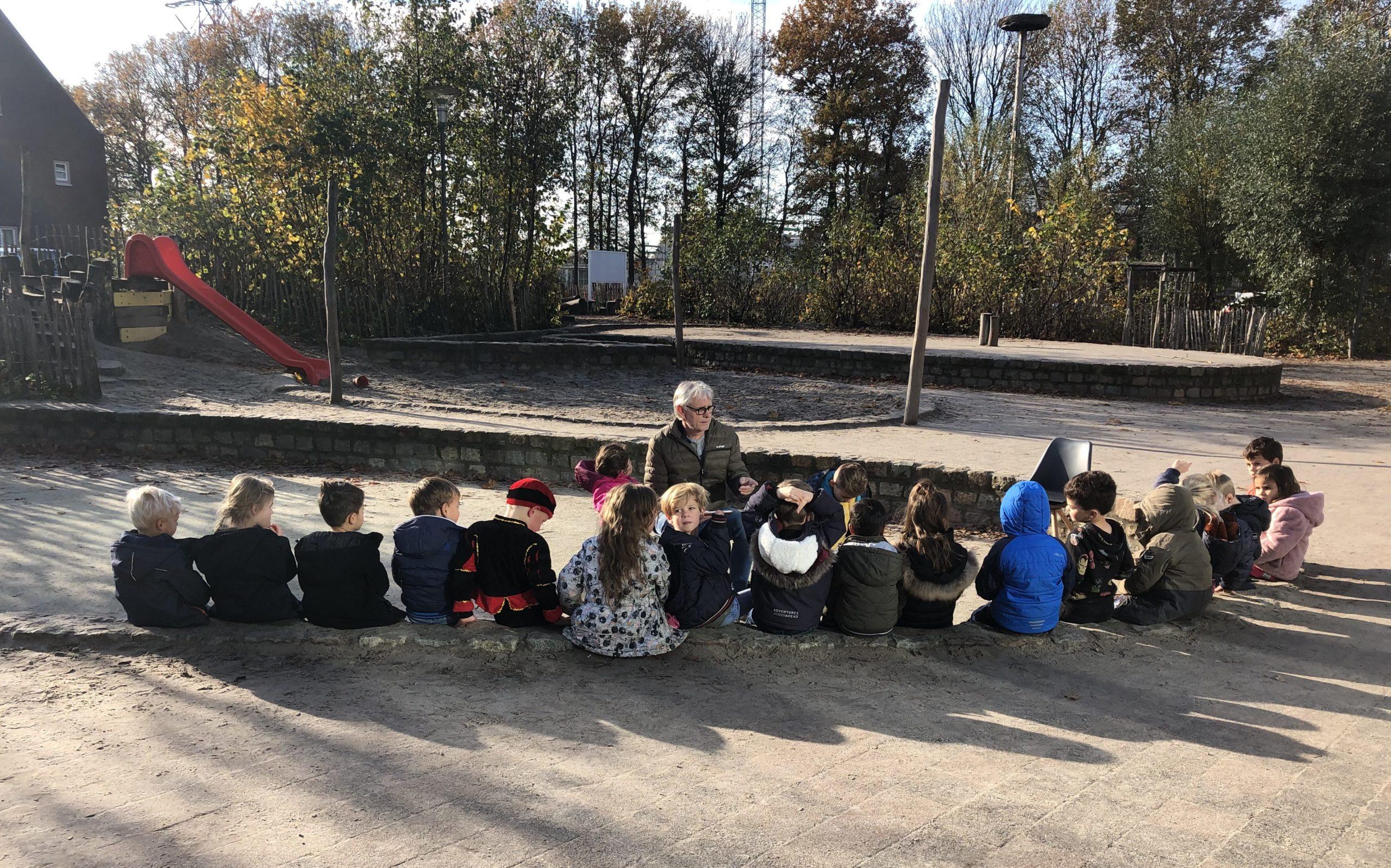 kinderen van basisschool Mondomijn luisteren naar opa Cees